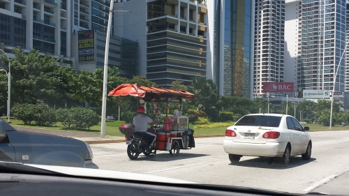 Pretty elabourate street vendor cart sharing the road.